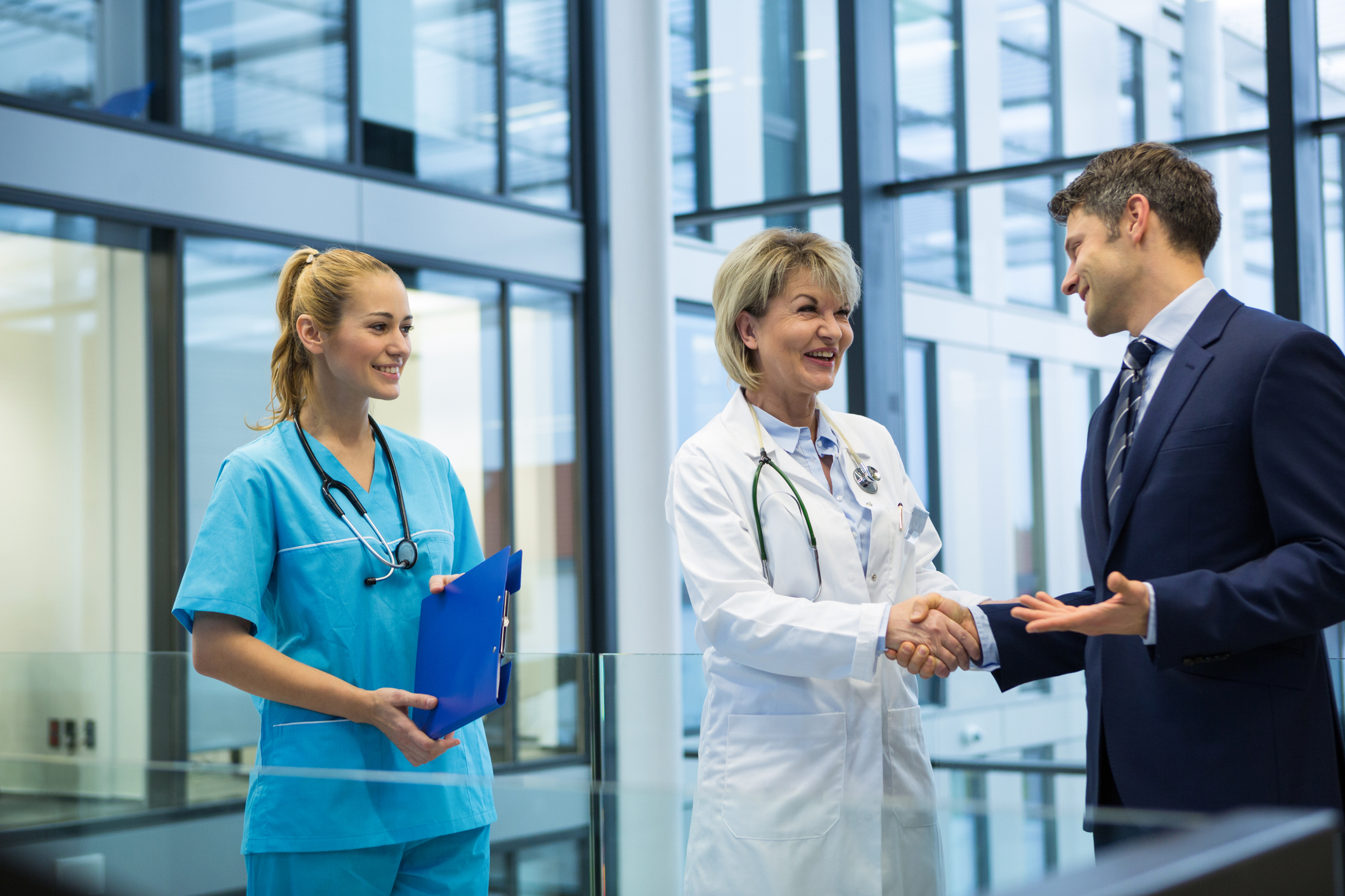 Female doctor providing physician coverage is shaking hands with businessman as healthcare worker in scrubs looks on.